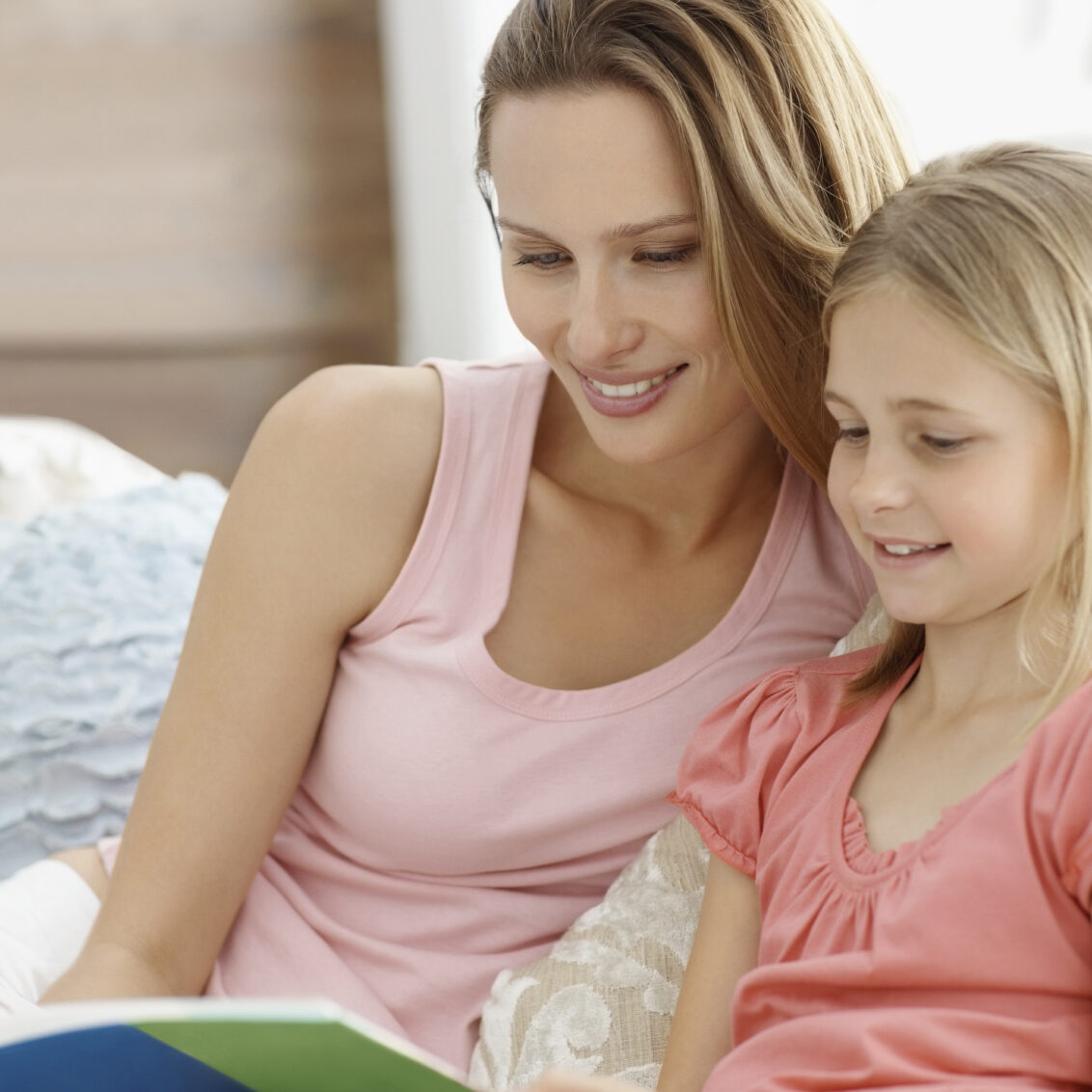 Portrait of a mother and daughter reading book together at home