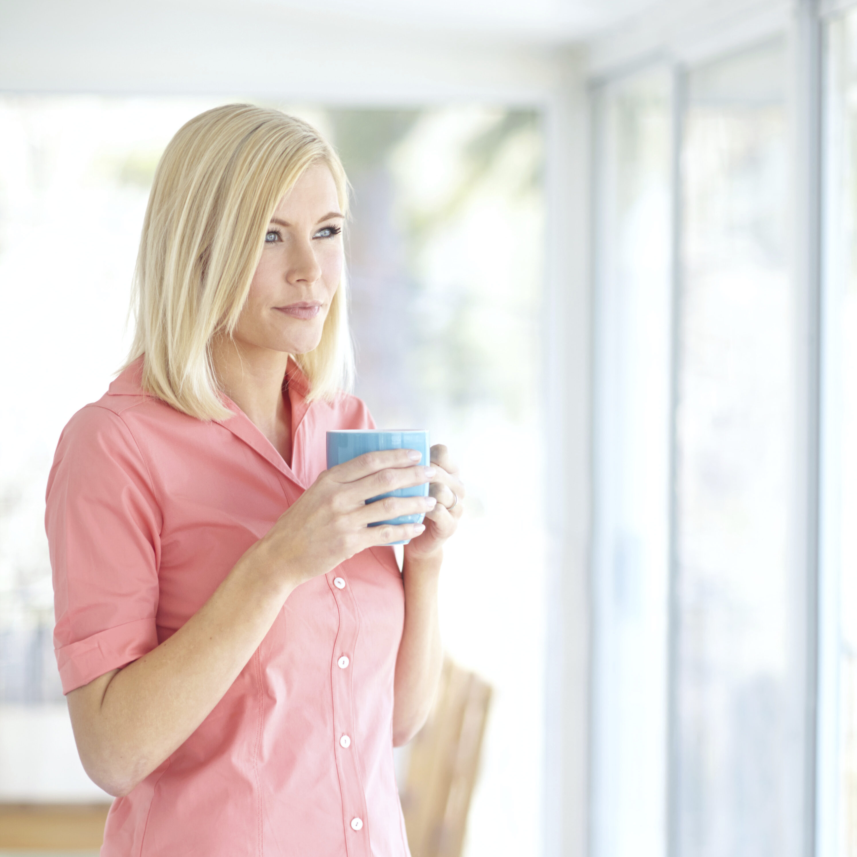 Thoughtful young blonde woman relaxing at home with a cup of coffee